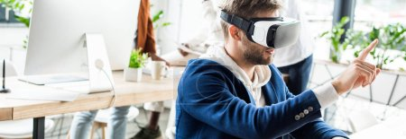 panoramic shot of young businessman touching something with finger while using vr headset in office