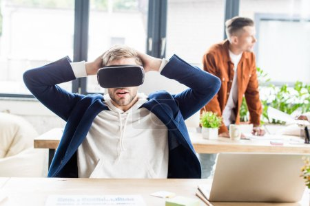 Photo for Young businessman using vr headset and holding hands behind head while sitting at workplace in office - Royalty Free Image