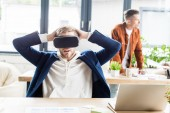 young businessman using vr headset and holding hands behind head while sitting at workplace in office