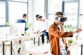 """Постер, картина, фотообои """"young businessman using vr headset and touching something with finger while multicultural colleagues working in office"""""""