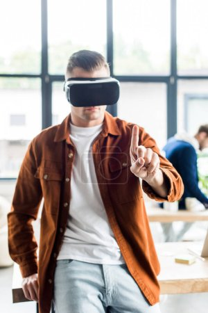 Photo for Young businessman touching something with finger while using virtual reality headset in office - Royalty Free Image