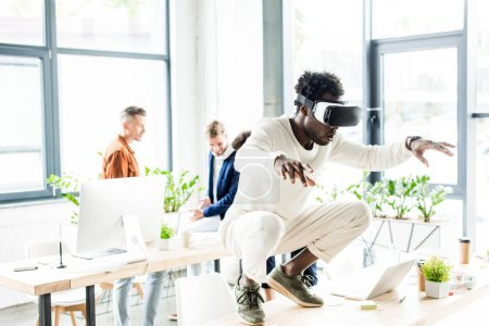 african american businessman squatting on table while using vr headset, and colleagues working in office