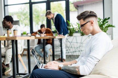 Photo pour Jeune homme d'affaires dans des lunettes assis dans un fauteuil doux et utilisant un ordinateur portable près de collègues multiculturels travaillant dans le bureau - image libre de droit