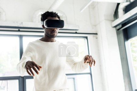 Photo for Young african american businessman using virtual reality headset in office - Royalty Free Image