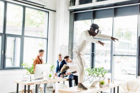 Photo pour Un homme d'affaires américain d'origine africaine utilisant un casque d'écoute et debout sur un bureau pendant que ses collègues travaillent au bureau - image libre de droit
