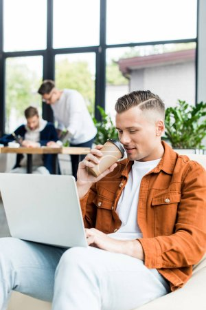 Photo for Young businessman drinking coffee to go and using laptop while working in office near colleagues - Royalty Free Image