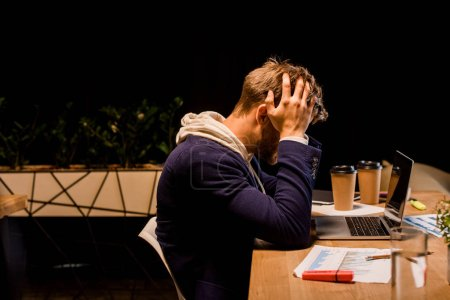 Photo pour Young exhausted businessman hollding hands on head while sitting at night in office near laptop and paper cups - image libre de droit
