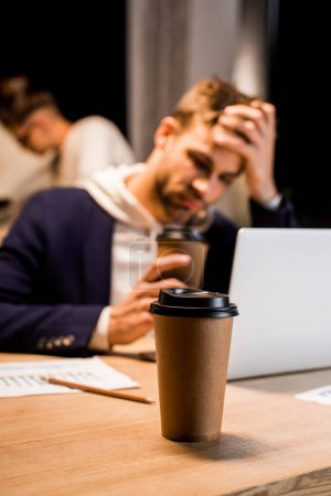 selective focus of disposable cup near exhausted businessman working at night in office