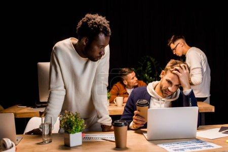 Photo pour Homme d'affaires afro-américain debout près de collègue épuisé tenant du café pour aller tout en travaillant la nuit au bureau - image libre de droit