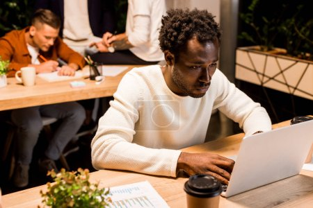 exhausted african american businessman using laptop while working at night in office near colleagues