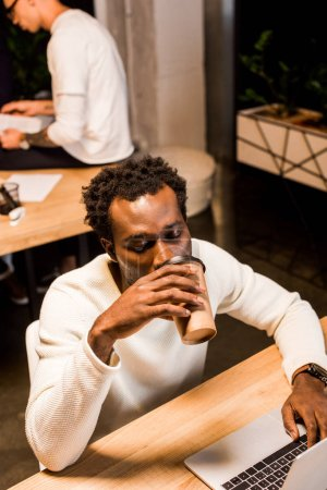 Photo for Tired african american businessman drinking coffee to go while working at night in office - Royalty Free Image