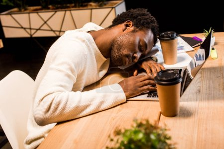 exhausted african american businessman sleeping at workplace near laptop and disposable cups at night in office