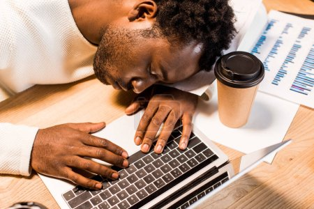 Photo for Tired african american businessman sleeping at workplace near laptop and disposable cup at night in office - Royalty Free Image