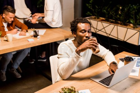 Photo for Tired african american businessman drinking coffee to go while sitting at workplace at night in office near colleagues - Royalty Free Image
