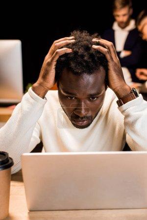 Photo pour Un homme d'affaires américain d'origine africaine, fatigué, se tenant la main sur la tête pendant qu'il travaillait de nuit au bureau - image libre de droit