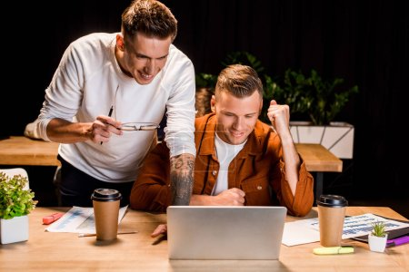 Photo pour Smiling businessmen looking at laptop while working at night in office - image libre de droit