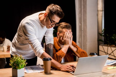 Photo pour Jeune homme d'affaires debout près de collègue épuisé couvrant le visage avec les mains tout en étant assis près d'un ordinateur portable dans le bureau - image libre de droit