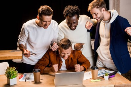 cheerful young businessmen standing near laptop and showing winner gesture at night in office