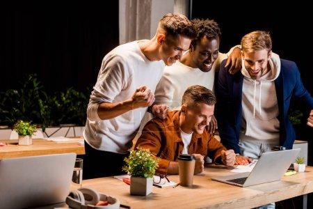 Photo pour Heureux jeunes hommes d'affaires regardant ordinateur portable et montrant geste gagnant la nuit au bureau - image libre de droit