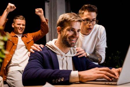 Photo pour Hommes d'affaires heureux à la recherche d'un ordinateur portable tout en travaillant la nuit au bureau - image libre de droit