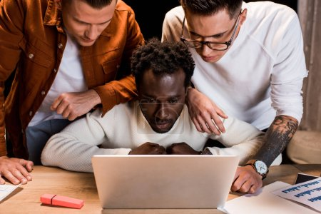 attentive multicultural businesspeople looking at laptop while working at night in office