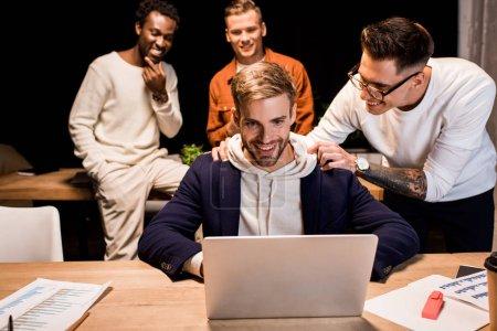 Foto de Feliz hombre de negocios tocando hombros de colega sentado cerca de portátil en la noche en la oficina - Imagen libre de derechos
