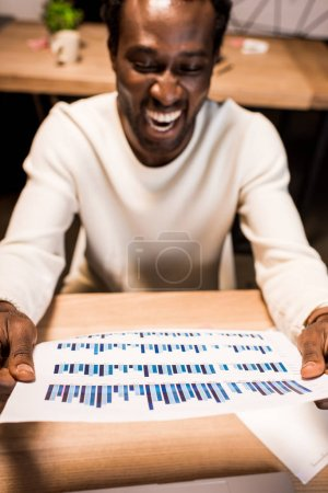 Photo for Selective focus of happy african american businessman holding paper with graphs and charts - Royalty Free Image
