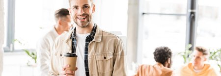 Photo for Panoramic shot of young businessman holding coffee to go and smiling at camera - Royalty Free Image
