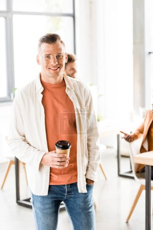 Photo for Young, handsome businessman in casual clothing holding coffee to go and smiling at camera - Royalty Free Image