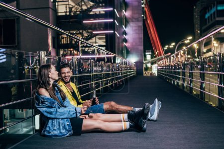 Photo for Side view of boyfriend with bottle and smiling girlfriend sitting in night city - Royalty Free Image