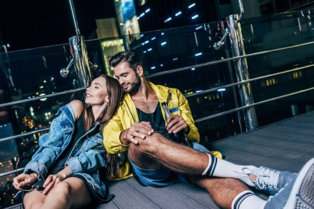 Photo for Attractive girlfriend lying on shoulder of her boyfriend with bottle in night city - Royalty Free Image