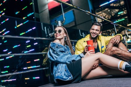 Photo for Handsome boyfriend and attractive girlfriend with plastic cups smiling in night city - Royalty Free Image