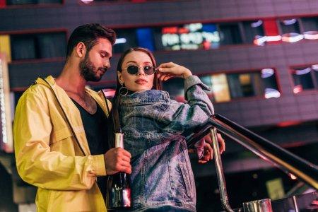 Photo pour Beau petit ami avec la bouteille étreignant la petite amie attirante dans la veste de denim dans la ville de nuit - image libre de droit