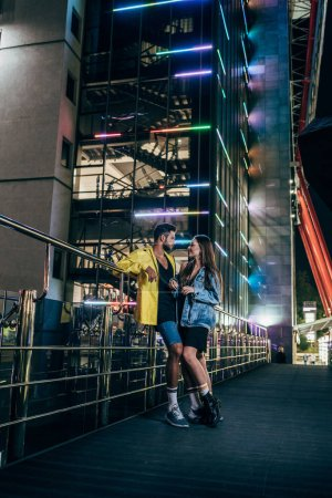 Photo for Side view of handsome boyfriend and attractive girlfriend smiling and talking in night city - Royalty Free Image