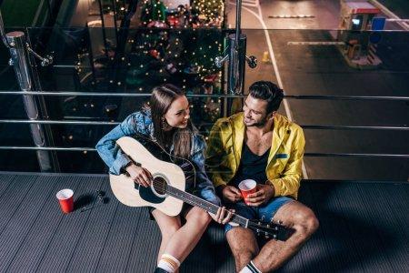 Photo pour Vue d'angle élevé du beau petit ami avec la tasse en plastique et la petite amie attirante jouant la guitare acoustique dans la ville de nuit - image libre de droit