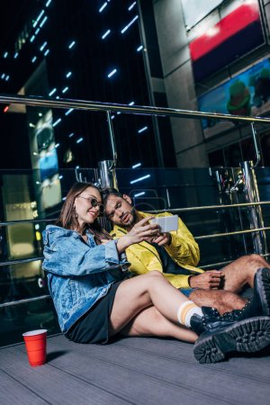 Photo for Handsome boyfriend and attractive girlfriend smiling and taking selfie in night city - Royalty Free Image