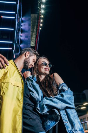 Photo for Low angle view of handsome boyfriend and attractive girlfriend smiling and hugging in night city - Royalty Free Image