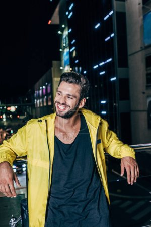 Photo for Handsome man in yellow jacket smiling and looking away in night city - Royalty Free Image