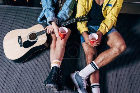 Photo for Cropped view of boyfriend and girlfriend holding plastic cups in night city - Royalty Free Image