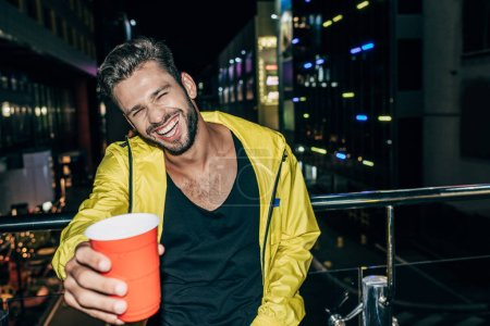 Photo for Handsome man in yellow jacket smiling and holding plastic cup in night city - Royalty Free Image