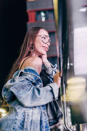 Photo for Attractive and smiling woman in denim jacket and glasses looking away in night city - Royalty Free Image