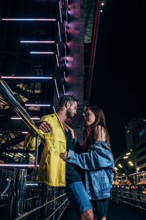 Photo for Side view of handsome boyfriend and attractive girlfriend in denim jacket hugging in night city - Royalty Free Image