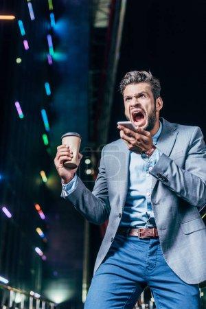 Photo pour Homme d'affaires beau en colère en tenue formelle parlant sur smartphone et tenant tasse de papier dans la ville de nuit - image libre de droit