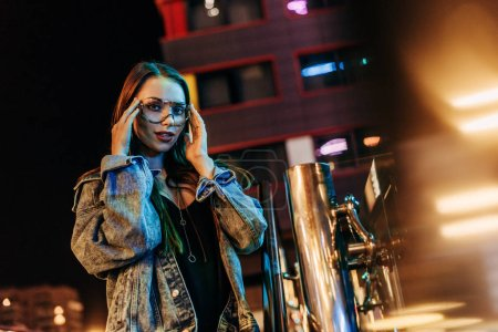 Photo for Attractive woman in denim jacket and glasses looking at camera in night city - Royalty Free Image