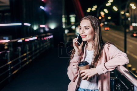 Photo for Attractive woman in pink jacket talking on smartphone and holding paper cup in night city - Royalty Free Image