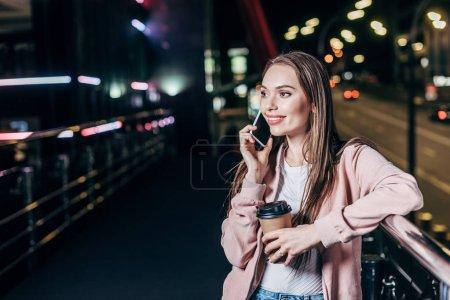 Photo pour Femme attirante dans la veste rose parlant sur le smartphone et retenant la tasse de papier dans la ville de nuit - image libre de droit
