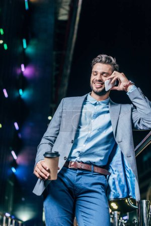 Photo for Low angle view of handsome businessman in formal wear talking on smartphone and holding paper cup in night city - Royalty Free Image
