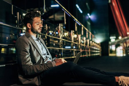 Photo pour Bel homme d'affaires en tenue formelle assis et utilisant un ordinateur portable dans la ville de nuit - image libre de droit