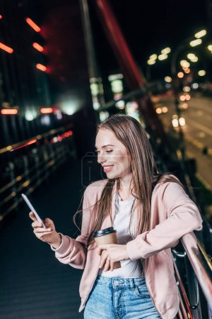 Photo for Smiling woman in pink jacket using smartphone and holding paper cup in night city - Royalty Free Image