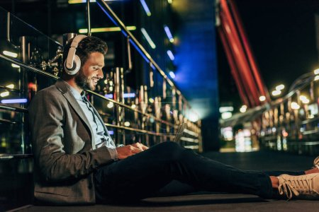 Photo for Handsome businessman in formal wear with headphones sitting and using laptop in night city - Royalty Free Image
